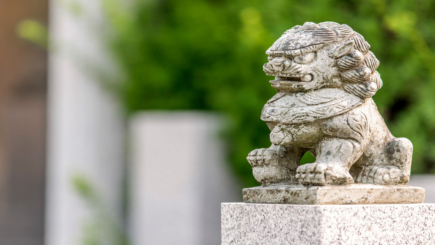 An intricate, stone lion statue sits regally atop a stone column.