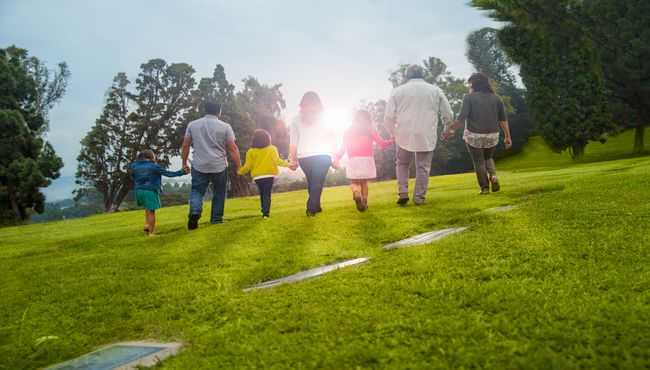 Three generations of a family walk toward the sun on a visit to their place of remembrance.
