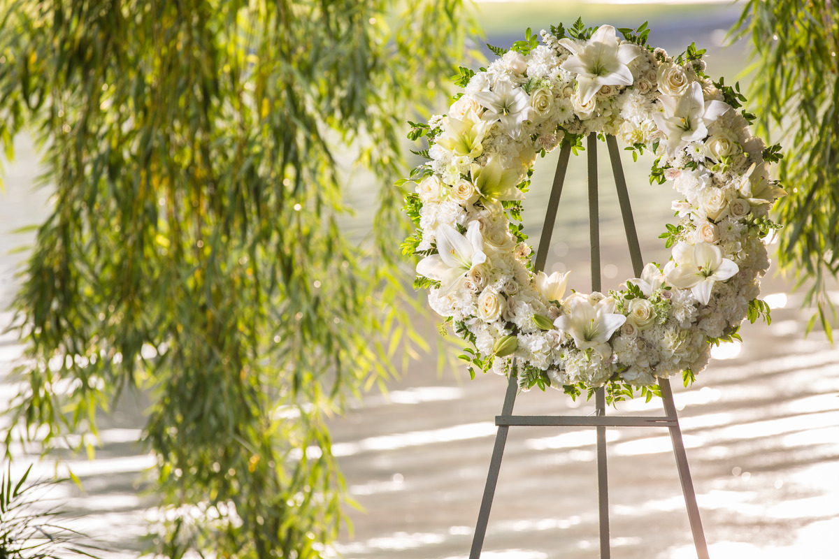 A white floral wreath near a willow tree and lake