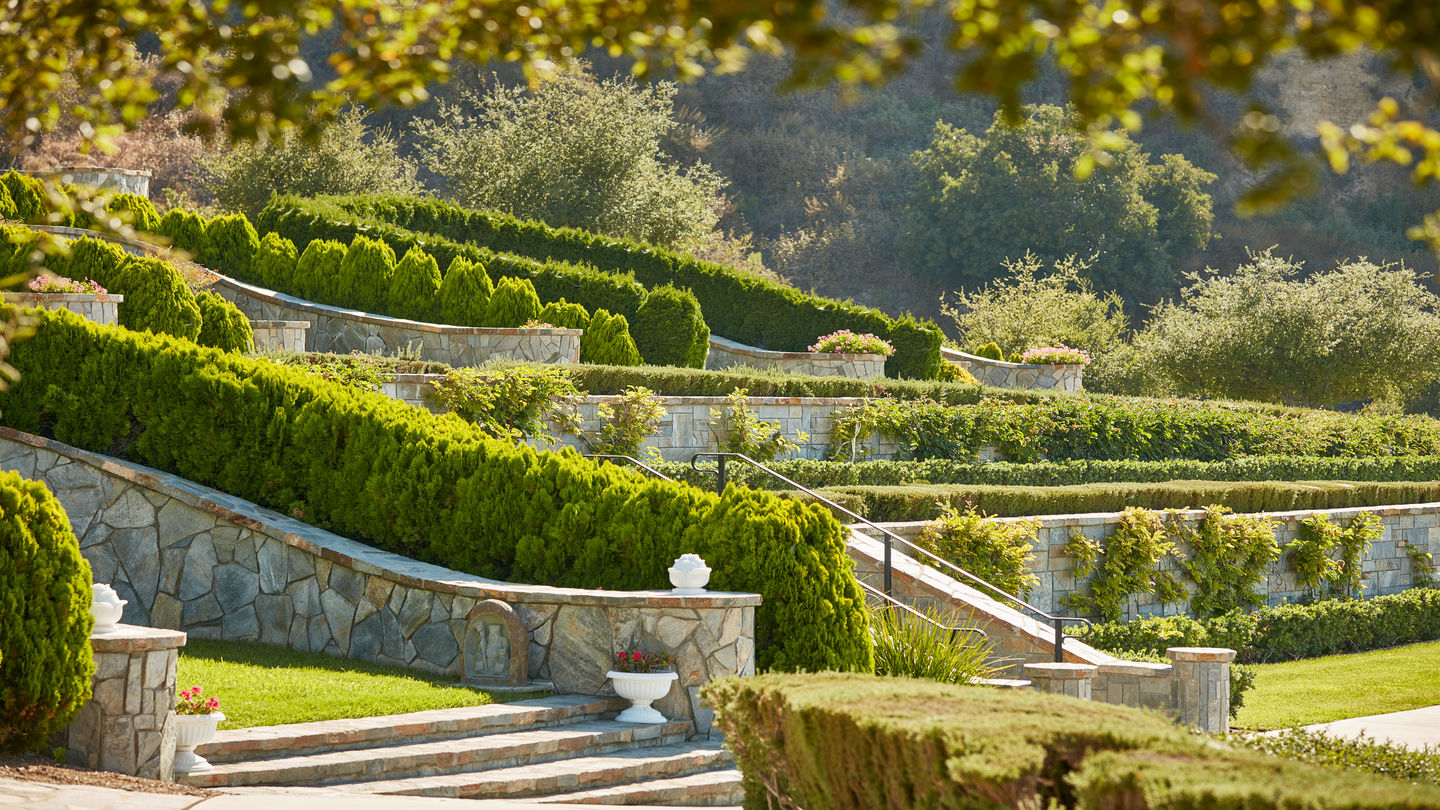 Masterfully trimmed hedges dress up this terraced garden containing several private and semi-private cemetery plots.