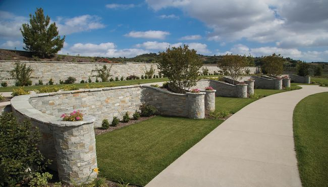 Stone-clad private estates along a curved pathway at Rose Hills Memorial Park in Whittier, CA.