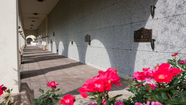 Outdoor mausoleum corridor with arched shadows and flowers in the foreground. Mission Hills at Rose Hills Memorial Park in Whittier, CA